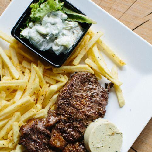 Ribeye met kruidenboter inclusief frites, salade en saus