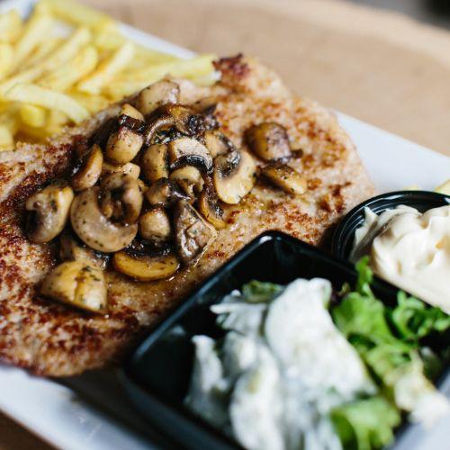Schnitzel met gebakken champignons inclusief frites, salade en saus